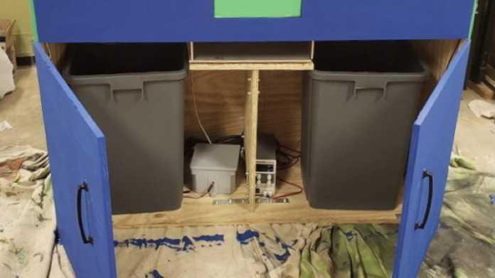 Eine blau gestrichene Holzkiste mit der Aufschrift Recycling. Hinter zwei geöffneten Türen sind zwei Mülleimer und Elektronik zu sehen.