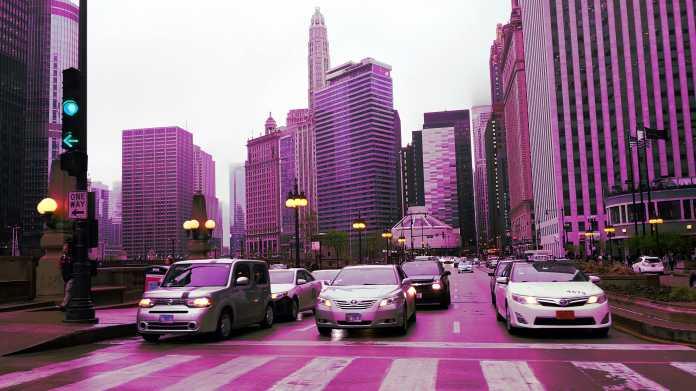 Farbverfälschte Aufnahme zeigt eine Grüne Ampel und mehrere Autos vor Hochhäusern Chicagos