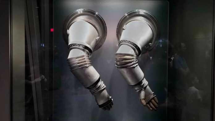 Metallene Arme eines Raumanzug-Prototypen hängen in einer Vitrine