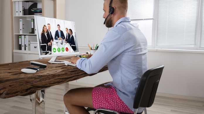 Mann in kurzer Hose und Hemd in Videokonferenz