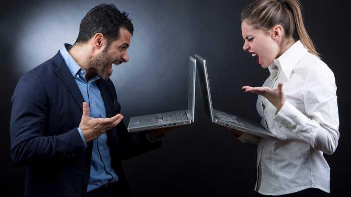 Mann und Frau mit Notebooks streiten
