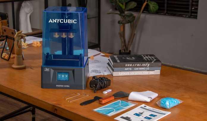 Auf einem braunen Tisch stehen ein 3D-Drucker mit blauer Verkleidung und Zubehörteile wie Netzteil und Spatel.