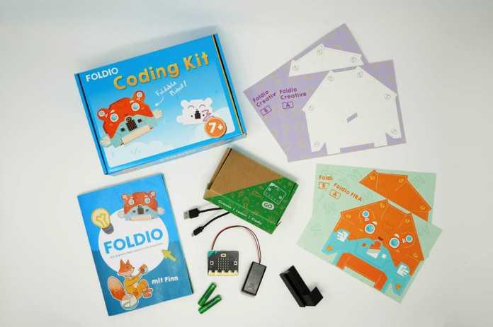 Inhalt des Foldio-Sets: vier Bastelbögen, ein Buch sowie ein BBC micro:bit mit Batteriehalter und Batterien.