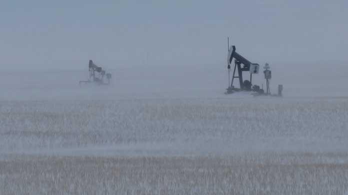 2 Erdgas-Pumpen in einem Feld in Schneesturm