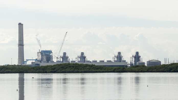 Rauchfänge und Türme eines Atomkraftwerks gesehen vom Wasser aus