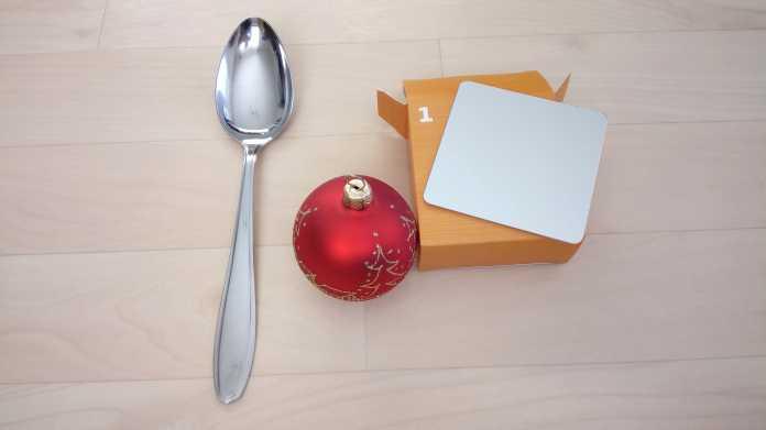 Ein silberner Löffel, eine rote Weihnachtsbaumkugel und ein kleiner, quadratischer Spiegel.