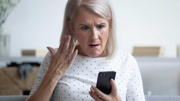 Seniorin ärgert sich über ihr Handy