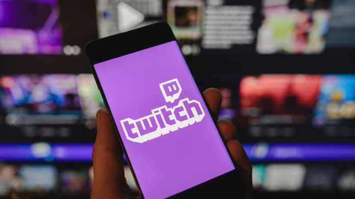 Smartphone mit dem Twitch-Logo auf dem Bildschirm vor einem verschwommenen Hintergrund mit mehreren Monitoren.