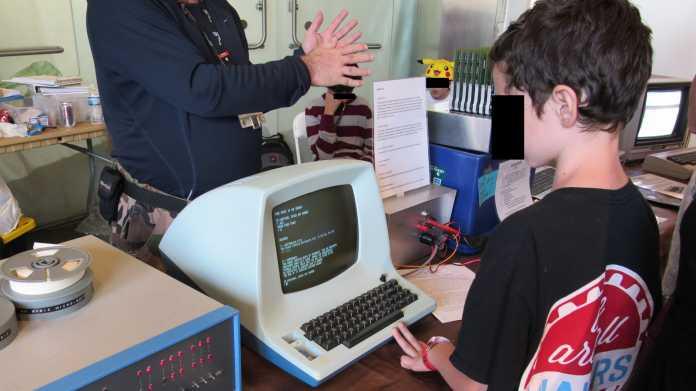 Alte Computer, drei Kinder - eines spielt ein Text Adventure Game