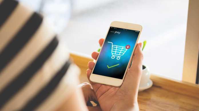 Eine Frau hält ein Handy, auf dessen Bildschirm ein Bezahlvorgang für einen Online-Einkauf zu sehen ist.