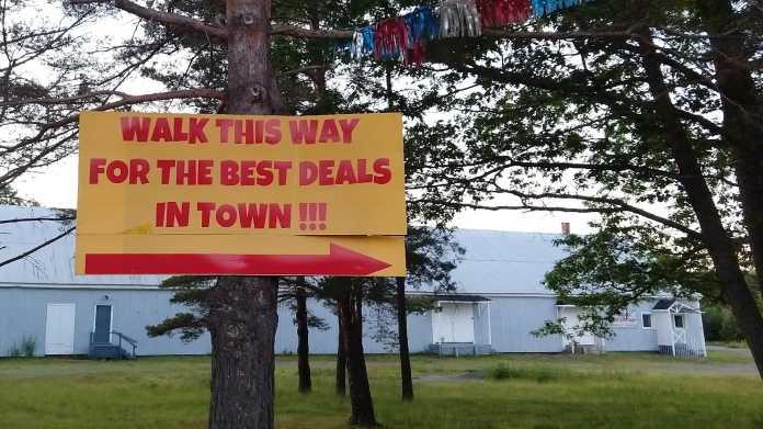 """Schild an Baum: """"Walk this way for the best deals in Town!!!"""""""
