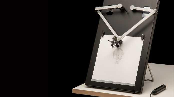 Auf einem Tisch steht ein schwarzer Kasten, auf dem ein weißes Papier eingeklemmt ist. Darüber halten zwei kleine Roboterarme einen Stift.
