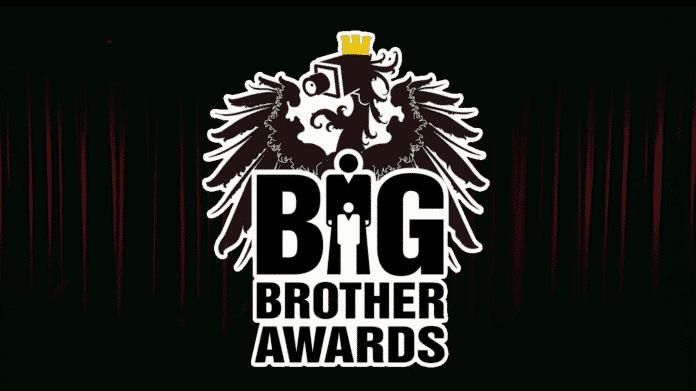 Logo der österreichischen Big Brother Awards, dahinter im Dunkeln roter Vorhang