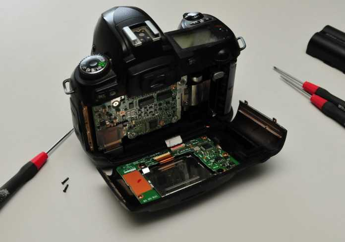 Nach Lösen von vier Schräubchen kann die Rückwand nach unten geklappt werden. Die Kamera sollte in dieser Arbeitsposition bleiben.