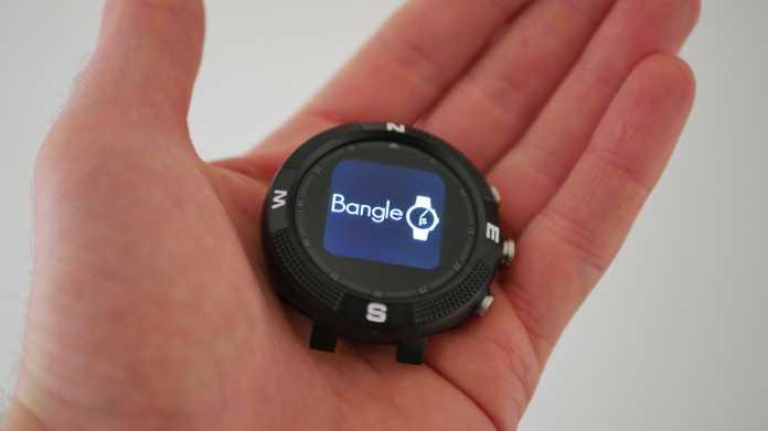 Eine Hand hält das runde Display einer schwarzen Smartwatch. Darauf steht: Bangle.js.