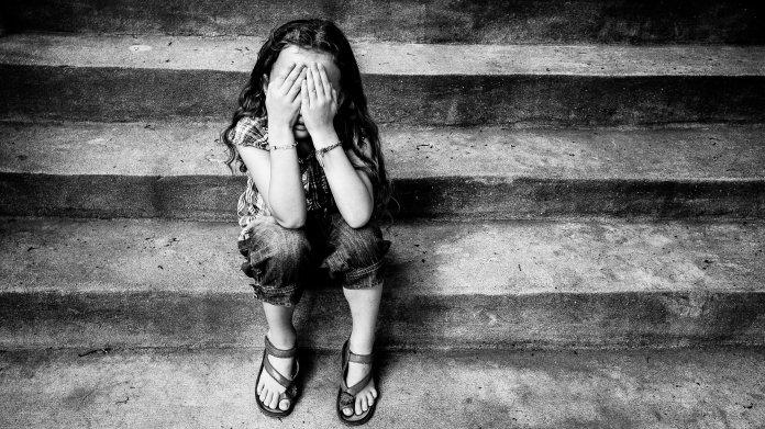 Auf Stufen sitzendes Mädchen schlägt die Hände vors Gesicht