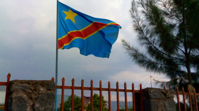 Fahne der DR Kongo weht auf einem Mast hinter einem Zaun