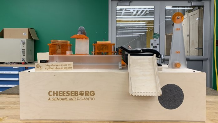 Maschine aus Holz: Oben hebt ein Arm Toastbrotscheiben und Käse. Ein Fließband transportiert sie in einen Sandwichgrill.