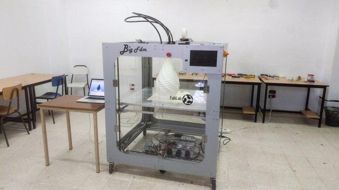 Ein riesiger 3D-Drucker neben Tischen und Stühlen.
