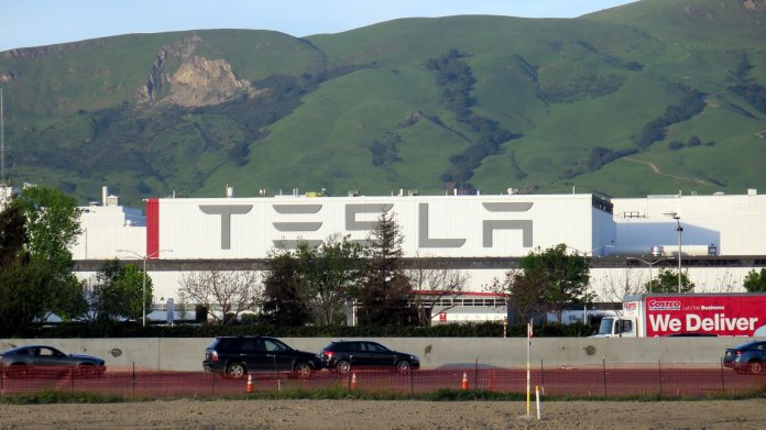 """Fabrikhalle mit Aufschrift """"Tesla"""", davor eine Autobahn"""