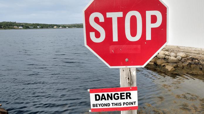 """Stoptafel mit Zusatzschild """"DANGER beyond this point"""" - dahinter Meereswasser"""