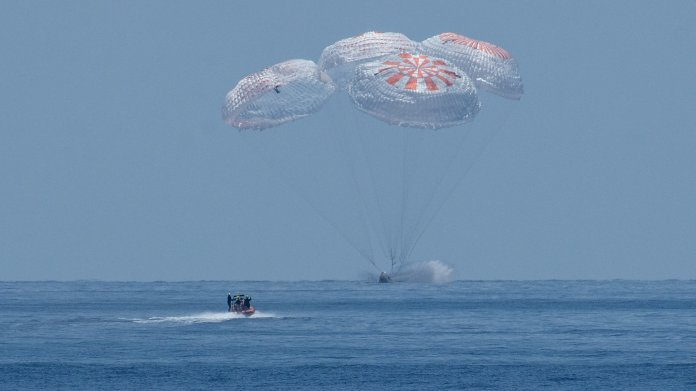 Kapsel mit 4 Fallschirmen knapp über dem Meer