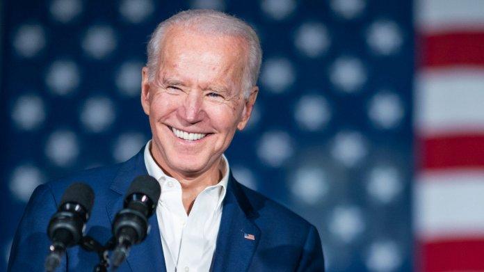 Jo Biden lächelnd vor zwei Mikrofonen