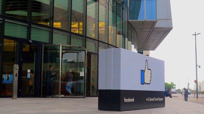 Glaspalast, davor großes Schild mit Facebook-Daumen