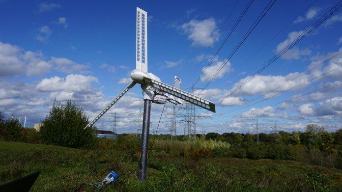 Kleine, weiße Windmühle vor blauem Himmel.