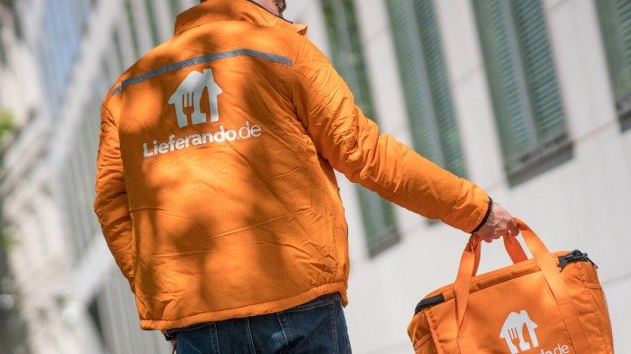 Mann in oranger Uniformjacke trägt eine orange Tasche