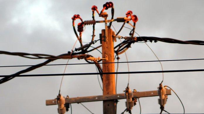 Stromkabel und Isolatoren an einem hölzernen Strommast