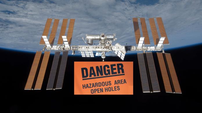 """ISS über der Erdkugel, davon ein Riesenschild """"Danger - Hazardour Area Open Holes"""""""