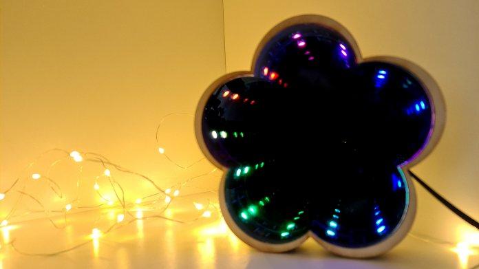 Ein Spiegel in Form einer fünfblättrigen Blume, in dem bunte LEDs in die Unendlichkeit gespiegelt werden.