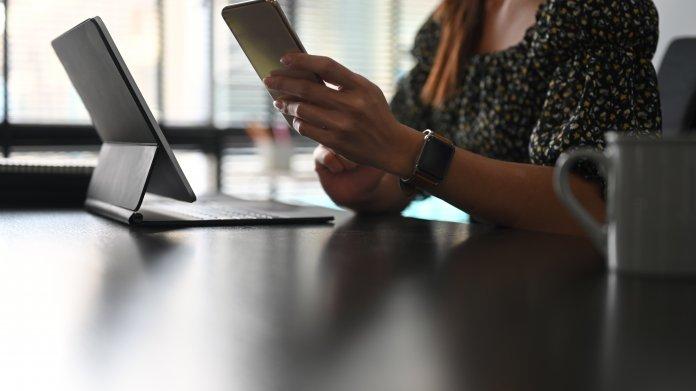 Mitarbeiterin an Handy und Notebook
