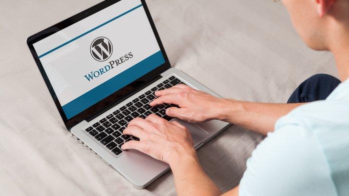 Wordpress-Logo auf dem Laptop einer Benutzerin