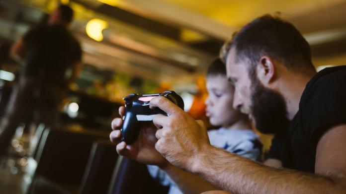 Ein bärtiger Mann und ein Knabe beim Computerspielen