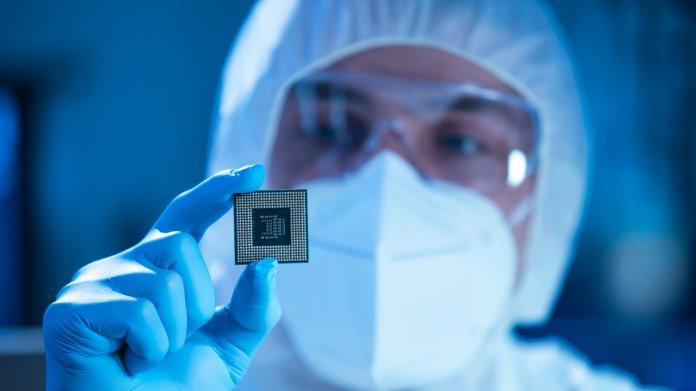 Mitarbeiter der Fertigung hält Mikrochip