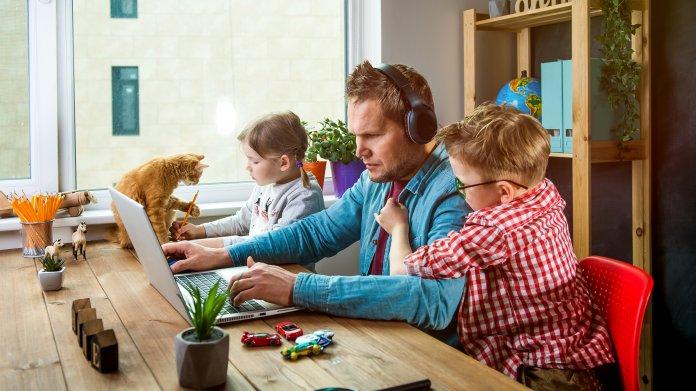 Vater im Homeoffice mit Kindern