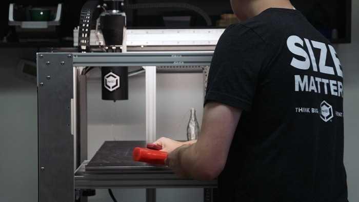Vor einem großen 3D-Drucker steht ein Mensch, mit dem Rücken zur Kamera.