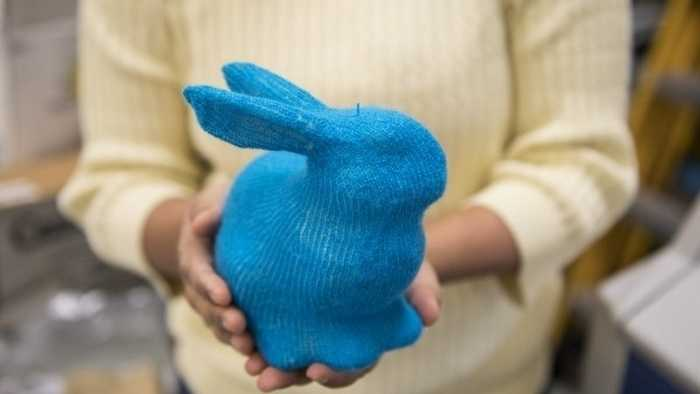 Zwei Hände halten einen blauen Hasen aus Strick