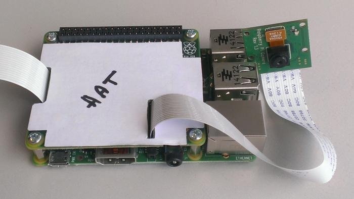 Ein grüner Raspberry Pi auf dem eine Platine befestigt ist. Auf ihr liegt ein weißer Zettel mit der Aufschrift HAT.