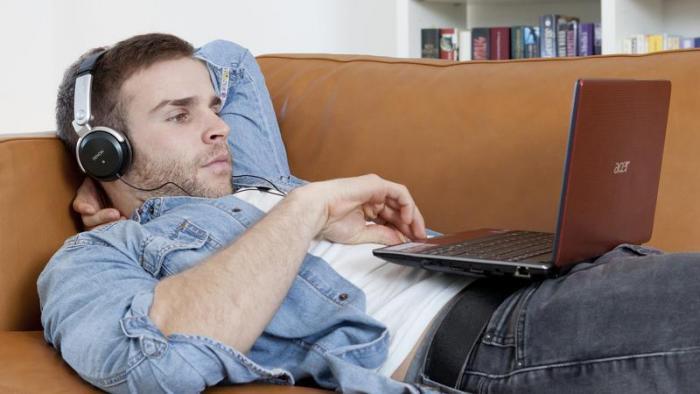Mann mit Kopfhöhrern und Laptop auf Sofa