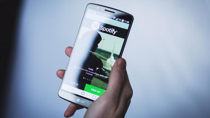 Hand hält Handy mit aktiver Spotify-App