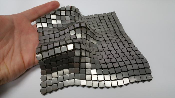 Hand hält Metallgewebe