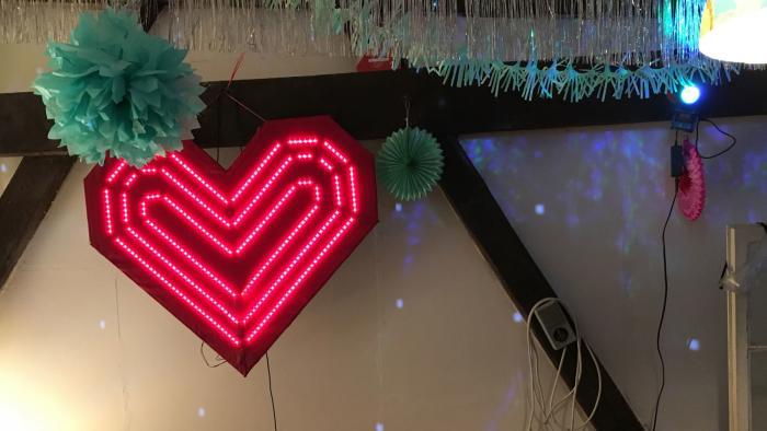 Ein großes leuchtendes rotes Herz hängt an einer weißen Wand mit Partydekoration