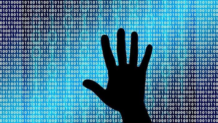 Schatten einer Hand, dahinter Binärcode