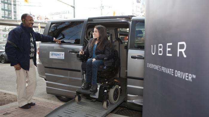 Rolli-Fahrerin gleitet über Rampe aus Uber-Van