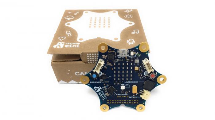 Blauer Mikrocontroller vor brauner Pappschachtel