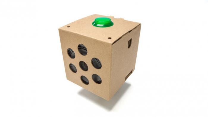 Ein brauner Pappwürfel mit grünem Button oben und Lautsprecher hinter großen Löchern an der Seite