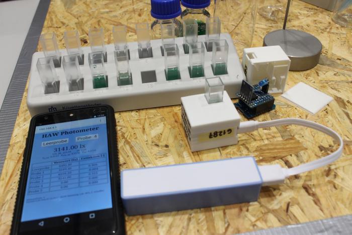 Ein Smartphone liegt neben einem weißen Kistchen und einer Powerbank, dahinter steht eine